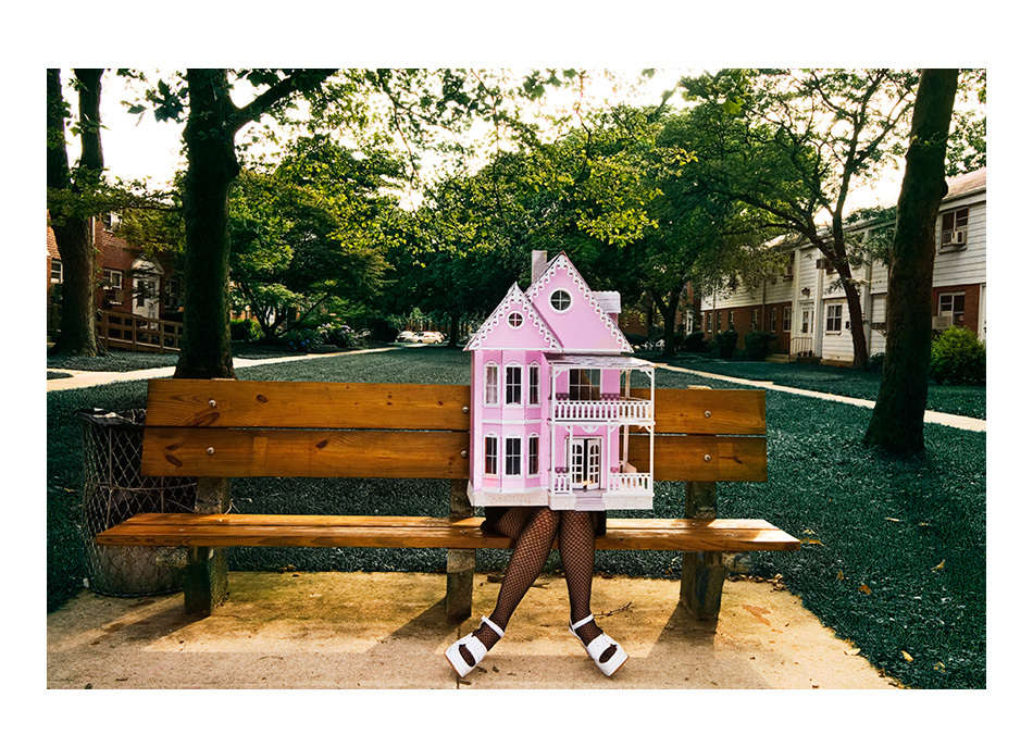 Artist Raven Schlossberg from a series on artists in New York wearing a doll house on bench at housing complex in Queens New York : Portraits-Keywording : NY - Portrait Photographer Video, Architectural, Corporate Editorial Location Photography